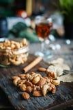 Acajounüsse, Walnüsse und Mandeln mit Whisky auf hölzernem backgrou Lizenzfreie Stockfotografie