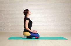 Acalme e concentrou a mulher que faz exercícios da ioga na pose dos lótus Imagem de Stock