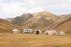 Acampamento da barraca com casas dos povos asiáticos nômadas locais em um vale bonito da montanha Imagem de Stock Royalty Free