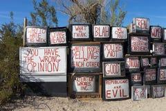 Acampamento do leste do artista de Jesus que exibe aparelhos de televisão reciclados com os slogan escritos em suas telas Imagens de Stock