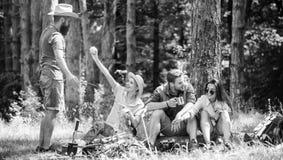 Acampamento e caminhada Amigos da empresa que relaxam e que t?m o fundo da natureza do piquenique do petisco Grande fim de semana imagem de stock
