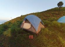 Acampamento nas montanhas Uma barraca do turista em um monte verde Uma sapata cor-de-rosa na frente da barraca Imagem de Stock