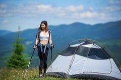 Acampamento próximo do caminhante da mulher nas montanhas com trouxa e as varas trekking na manhã foto de stock