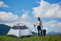 Acampamento próximo do turista da mulher nas montanhas com trouxa e as varas trekking na manhã fotos de stock