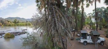 Acampamento surpreendente pelo rio de Kunene nas quedas de Epupa, ao norte do Na Fotos de Stock