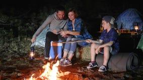 Acampamento, vídeo feliz do registro da família no telefone celular perto da fogueira na floresta, mum e filho e paizinho com lâm video estoque