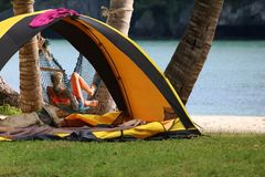 Acampando en la playa, muchacha que se relaja en la hamaca cerca de la tienda Fotos de archivo libres de regalías