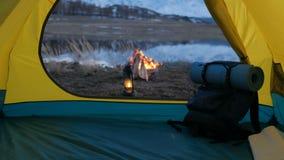Acampando en las montañas, el fuego del campo y la tienda en la puesta del sol 20s 4k metrajes