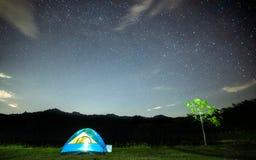 Acampar em um feriado com luz das estrelas na noite, com as temperaturas frescas que estão sendo tomadas bem com as lentes largas imagens de stock