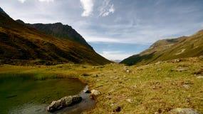 Acampar em um lugar do resto pelo lago em cumes suíços imagens de stock royalty free