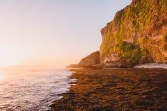 Acantilado con las rocas, el océano y colores de la puesta del sol en Bali Imagenes de archivo