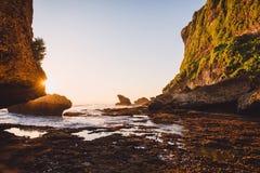 Acantilado con las rocas, las piedras, el océano de la marea baja y colores de la puesta del sol en Bali Imagenes de archivo