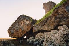 Acantilado con las rocas, las piedras y los colores de la puesta del sol en Bali Foto de archivo