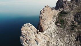Acantilado de piedra maravilloso de la montaña de la roca en el agua azul profunda tranquila del lago Baikal en horizonte aéreo d metrajes