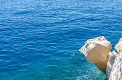 Acantilado o repisa de piedra de la roca sobre el mar azul foto de archivo libre de regalías
