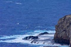 Acantilado rocoso lavado golpeando ondas y espuma Imagenes de archivo