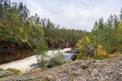 Acantilado rojo, pared de piedra, bosque, cascada y opinión salvaje del río en otoño Foto de archivo