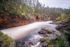 Acantilado rojo, pared de piedra, bosque, cascada y opinión salvaje del río en otoño Foto de archivo libre de regalías