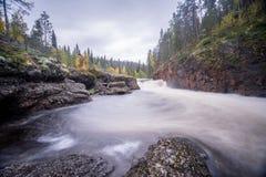 Acantilado rojo, pared de piedra, bosque, cascada y opinión salvaje del río en otoño Fotos de archivo