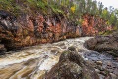 Acantilado rojo, pared de piedra, bosque, cascada y opinión salvaje del río en otoño Imagen de archivo libre de regalías