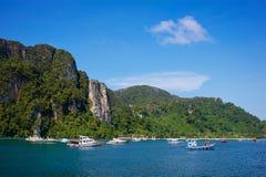 Acantilado y el mar claro con la isla de Phi Phi de los barcos en el sur de Tailandia Foto de archivo libre de regalías