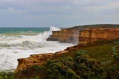 Acantilados de la piedra arenisca con las ondas grandes en el gran camino del océano Foto de archivo