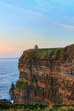 Acantilados de Moher con la torre en la puesta del sol en Irlanda. Fotografía de archivo