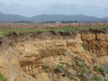 Acantilados dentados coloreados arena a lo largo de la Costa del Pacífico de Californa con las montañas en el fondo Imagen de archivo