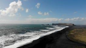 Acantilados negros de la playa de la arena aéreos en Islandia almacen de video