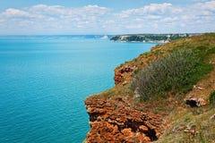 Acantilados rojos sobre el mar azul Imagen de archivo libre de regalías