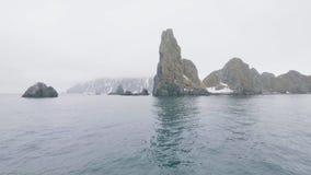 Acantilados y montañas rocosos con los picos nevosos en agua de mar del invierno almacen de metraje de vídeo