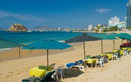 Acapulco Beach. Umbrellas, chase, chairs and tables with Great view of Acapulco Bay, Mexico Royalty Free Stock Photos