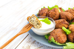 Acaraje or akara snack with green salad and sour cream. Brazilian acaraje or Nigerian akara snack with black pease or beans; served with green salad and sour Stock Photography