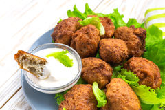 Acaraje or akara snack with green salad and sour cream. Brazilian acaraje or Nigerian akara snack with black pease or beans; served with green salad and sour Stock Image