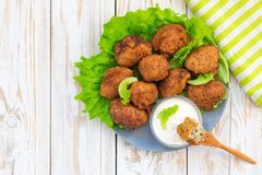 Acaraje or akara snack with green salad and sour cream. Brazilian acaraje or Nigerian akara snack with black pease or beans; served with green salad and sour Royalty Free Stock Photo