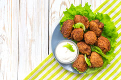Acaraje or akara snack with green salad and sour cream. Brazilian acaraje or Nigerian akara snack with black pease or beans; served with green salad and sour Royalty Free Stock Photos