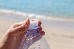 Acaricie la botella con agua en el mar con el enchufe cerrado de la mano Imágenes de archivo libres de regalías