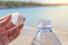Acaricie la botella con agua en el mar con el enchufe cerrado de la mano en beackground Imagen de archivo