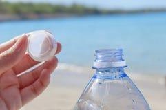 Acaricie la botella con agua en el mar con la mano que sostiene el enchufe Foto de archivo libre de regalías