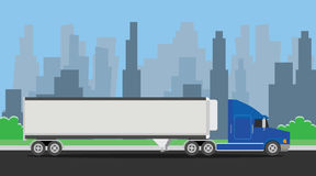 Acarree el transporte azul del remolque en la carretera con el fondo de la ciudad Imagen de archivo