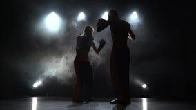 Accès le type et la fille sur les pattes de boxe Lumière par derrière Fumez le fond Silhouette clips vidéos