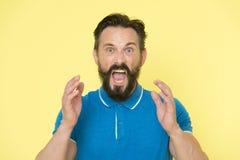 Accablé avec des émotions Position criarde de cri belle d'homme mûr sur le fond jaune Homme barbu photo libre de droits