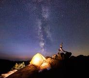 Accampandosi alla notte su formazione rocciosa Tenda turistica e donna che fanno yoga sulla cima della montagna Fotografia Stock