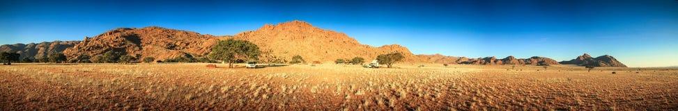 Accampandosi nel deserto con i camioncini e le tende Sera di tramonto Immagini Stock Libere da Diritti