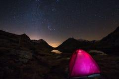 Accampandosi sotto il cielo stellato e l'arco della Via Lattea ad elevata altitudine sulle alpi francesi italiane Tenda d'ardore  Immagine Stock