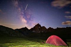 Accampandosi sotto il cielo stellato e Via Lattea ad elevata altitudine sulle alpi Tenda illuminata nella priorità alta e nel pic Fotografia Stock Libera da Diritti