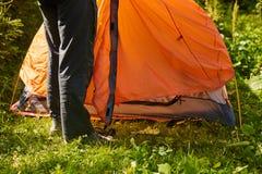 Accampi nella tenda - turista che mette una tenda sul campeggio Due uomini hanno installato una tenda nel bello posto nella fores Fotografia Stock
