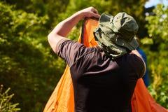 Accampi nella tenda - turista che mette una tenda sul campeggio Due uomini hanno installato una tenda nel bello posto nella fores Fotografie Stock Libere da Diritti
