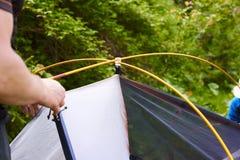 Accampi nella tenda - turista che mette una tenda sul campeggio La fine sulle mani del ` s dell'uomo tiene una tenda mentre insta Immagini Stock