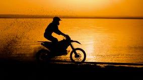 Accantonare estremo della motocicletta fuori strada Motociclista al tramonto vicino al fiume Bici estrema di motocross, sporcizia stock footage